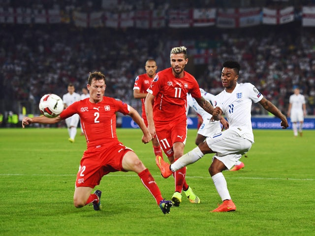Raheem Sterling of England shoots past Stephan Lichtsteiner (2) and Valon Behrami of Switzerland (11) during the UEFA EURO 2016 Group E qualifying match between Switzerland and England at St Jakob-Park on September 8, 2014