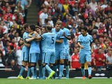 Martin Demichelis of Manchester City is congratulated by team-mates after scoring during the Barclays Premier League match between Arsenal and Manchester City at Emirates Stadium on September 13, 2014