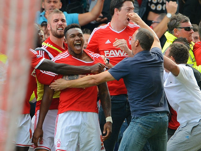 Britt Assombalonga of Forest celebrates scoring to make it 1-0 dwith team mates and fans during the Sky Bet Championship match between Nottingham Forest and Derby County at the City Ground on September 14, 2014