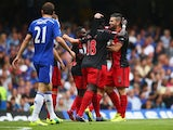 Bafetibis Gomis and Jordi Amat of Swansea City celebrate as John Terry of Chelsea scores an own goal for their first goal during the Barclays Premier League match between Chelsea and Swansea City at Stamford Bridge on September 13, 2014