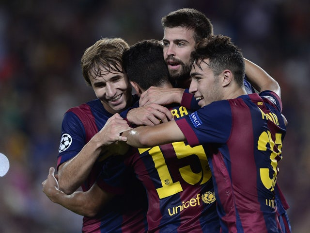 Barcelona's defender Gerard Pique celebrates with Barcelona's midfielder Sergi Samper and Barcelona's forward Munir after scoring during the UEFA Champions League football match FC Barcelona vs APOEL FC at the Camp Nou stadium in Barcelona on September 17