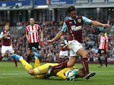 Vito Mannone of Sunderland dives to make a save at the feet of George Boyd of Burnley during the Barclays Premier League match between Burnley and Sunderland at Turf Moor on September 20, 2014