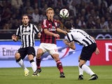 AC Milan's japanese forward Keisuke Honda (C) fights for the ball with Juventus defender Leonardo Bonucci on September 20, 2014