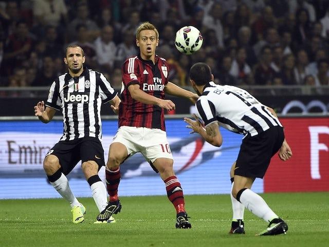 AC Milan's japanese forward Keisuke Honda (C) fights for the ball with Juventus defender Leonardo Bonucci on September 20, 2014