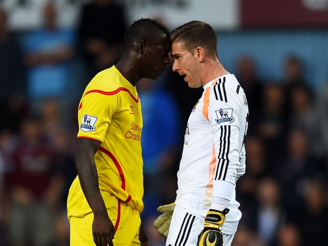 Mario Balotelli of Liverpool and Adrian of West Ham clash following a heavy tackle by Balotelli on Adrian during the Barclays Premier League match between West Ham United and Liverpool at Boleyn Ground on September 20, 2014