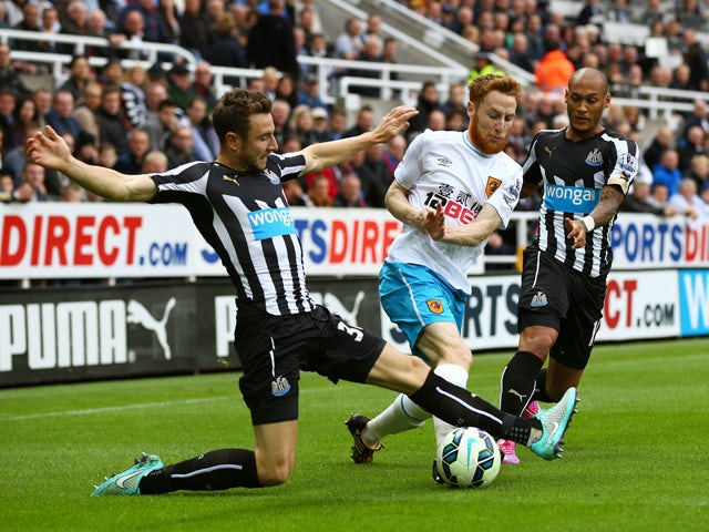 Stephen Quinn of Hull City is tackled by Paul Dummett of Newcastle United during the Barclays Premier League match between Newcastle United and Hull City at St James' Park on September 20, 2014