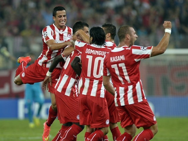 Olympiakos players celebrate after scoring during the Champions League group A fooball match at the Karaiskaki stadium in Piraeus near Athens on September 16, 2014