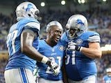 Reggie Bush #21 of the Detroit Lions celebrates with teammates Cornelius Lucas #77 and Dominic Raiola #51 after scoring on a 21 yard touchdown against the Green Bay Packers on September 21, 2014