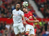 Raniere Sandro of QPR goes up for a header with Daley Blind of Manchester United during the Barclays Premier League match between Manchester United and Queens Park Rangers at Old Trafford on September 14, 2014