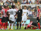 Swansea City`s Ivorian striker Wilfried Bony receives a red card from referee Jon Moss after making a second bookable tackle on Southampton`s Maya Yoshida during the English Premier League football match between Swansea City and Southampton at the Liberty