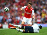 Mesut Ozil of Arsenal in action against Danny Rose of Spurs during the Barclays Premier League match between Arsenal and Tottenham Hotspur at Emirates Stadium on September 27, 2014