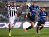 Juventus' defender Giorgio Chiellini fights for the ball with Atalanta's Argentinian forward German Gustavo Denis during the Italian Serie A football match Atalanta Vs Juventus on September 27, 2014