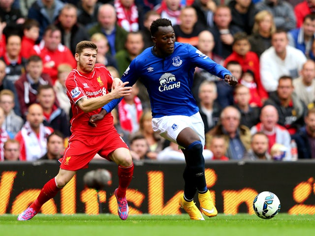 Romelu Lukaku of Everton holds off the challenges from Alberto Moreno of Liverpool during the Barclays Premier League match between Liverpool and Everton at Anfield on September 27, 2014