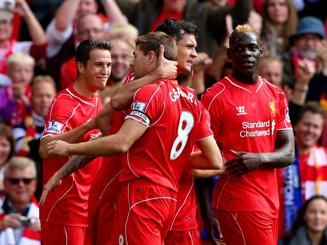 Steven Gerrard #8 of Liverpool is congratulated by teammates after scoring the opening goal from a free kick during the Barclays Premier League match between Liverpool and Everton at Anfield on September 27, 2014