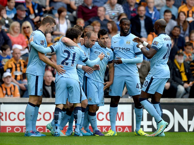 Sergio Aguero of Manchester City celebrates with team-mates after scoring the opening goal during the Barclays Premier League match between Hull City and Manchester City at KC Stadium on September 27, 2014