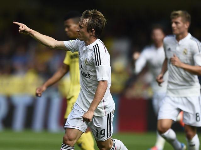 Real Madrid's Croatian midfielder Luka Modric celebrates after scoring during the Spanish league football match Villarreal CF vs Real Madrid CF at El Madrigal stadium in Villareal on September 27, 2014