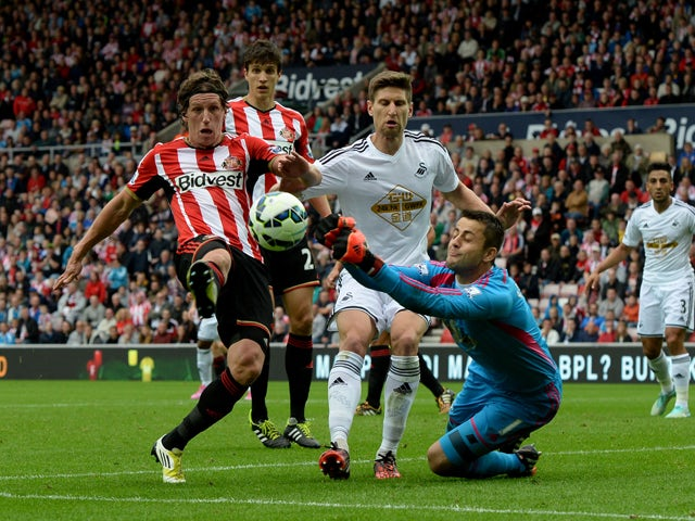 Billy Jones of Sunderland and Lukasz Fabianski of Swansea City battle for the ball during the Barclays Premier League match between Sunderland and Swansea City at Stadium of Light on September 27, 2014