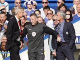 Chelsea's Portuguese manager Jose Mourinho (R) and Arsenal's French manager Arsene Wenger (L) are kept apart by the fourth official Jonathan Moss during the English Premier League match on October 5, 2014