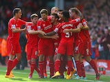 Adam Lallana of Liverpool is congratulated by team mates on scoring the opening goal during the Barclays Premier League match between Liverpool and West Bromwich Albion at Anfield on October 4, 2014