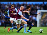 David Silva of Manchester City runs with the ball past Philippe Senderos of Aston Villa during the Barclays Premier League match between Aston Villa and Manchester City at Villa Park on October 4, 2014