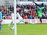 Papiss Demba Cisse of Newcastle United (R) scores their second past goalkeeper Lukasz Fabianski of Swansea City during the Barclays Premier League match between Swansea City and Newcastle United at Liberty Stadium on October 4, 2014