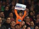 A young Newcastle fan holds up a sign calling for Alan Pardew, manager of Newcastle United, to be sacked during the Barclays Premier League match between Stoke City and Newcastle United at Britannia Stadium on September 29, 2014