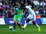 Wilfried Bony of Swansea City shoots past Paul Dummett of Newcastle United to score their first goal during the Barclays Premier League match between Swansea City and Newcastle United at Liberty Stadium on October 4, 2014