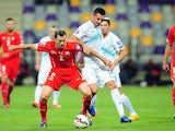 Switzerland's defender Stephan Lichtensteiner (L) vies for the ball with Slovenia's midfielder Andraz Kirm (2ndR) during the Euro 2016 qualifying match on October 9, 2014