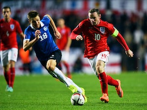 Wayne Rooney of England is pursued by Karol Mets of Estonia during the EURO 2016 Qualifier match between Estonia and England at A. Le Coq Arena on October 12, 2014