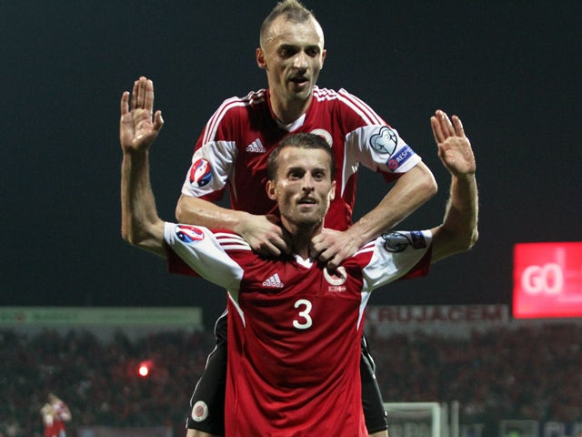Albania's Ermir Lenjani and Ansi Agolli celebrate after scoring during the Euro 2016 qualifying round football match between Albania and Denmark at the Elbasan Arena Stadium, on October 11, 2014