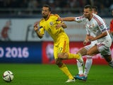Romania's midfielder Lucian Sanmartean (L) and Hungary's defender Tamas Kadar vie for the ball during the Euro 2016 Group F qualifying football match on October 11, 2014