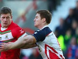 Larne Patrick of Wales is held up by Mark Offerdahl of USA during the Rugby League World Cup Group D match between Wales and USA at the Glyndwr University Racecourse Stadium on November 3, 2013