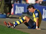 Arsenal's Mesut Ozil sits down off the pitch with an injury during the Premier League match against Leicester City on August 31, 2014