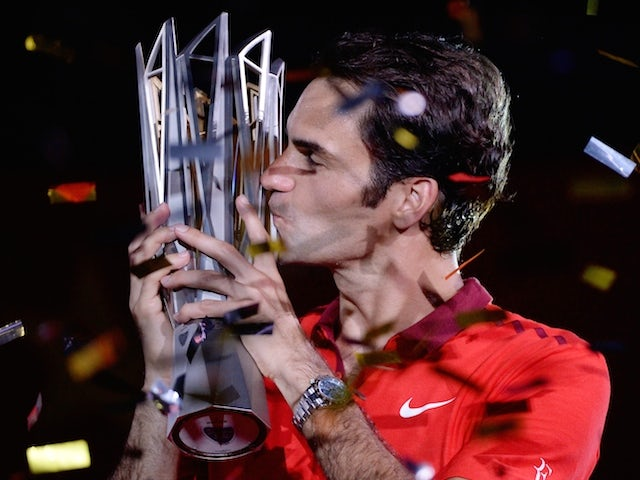 Roger Federer of Switzerland kisses the trophy after winning the Shanghai Masters on October 12, 2014