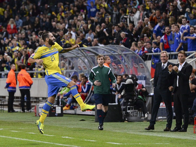 Sweden's midfielder Jimmy Durmaz celebrates in front of his head coach Erik Hamren after scoring a goal during the Euro 2016 Group G qualifying football match Sweden vs Liechtenstein at the Friends Arena in Solna, near Stockholm on October 12, 2014