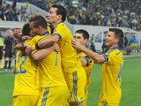 Ukraine's midfielder Serhiy Sydorchuk is embraced by forward Andrei Yarmolenko and other teammates after he scored during the UEFA 2016 European Championship qualifying round Group C match Ukraine vs Macedonia in Lviv on October 12, 2014