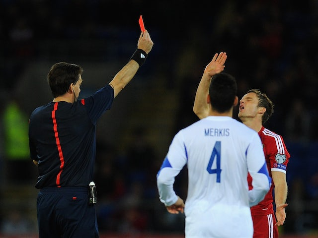 Wales player Andy King receives a straight red card from referee Manuel Grafe for a foul on Constantinos Makridis of Cyprus during the EURO 2016 Qualifier match on October 13, 2014