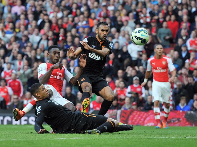 Arsenal's English striker Danny Welbeck scores their second goal past Hull City's English defender Curtis Davies and Hull City's Egyptian midfielder Ahmed Elmohamady during their English Premier League football match against Hull City at the Emirates Stad