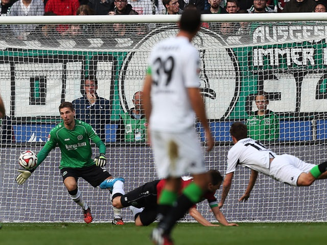 Monchengladbach's striker Max Kruse scores his team's opening goal against Hanover's goalkeeper Ron-Robert Zieler during the German First division Bundesliga football match Hannover 96 vs Borussia Moenchengladbach on October 18, 2014