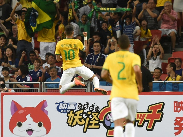 Brazil's forward Neymar celebrates his first goal in a friendly football match against Japan team at the National stadium in Singapore on October 14, 2014
