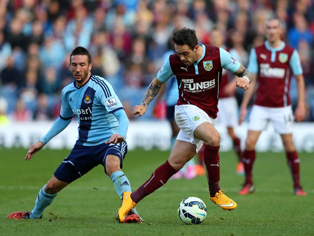 Danny Ings of Burnley is challenged by Morgan Amalfitano of West Ham during the Barclays Premier League match between Burnley and West Ham United at Turf Moor on October 18, 2014