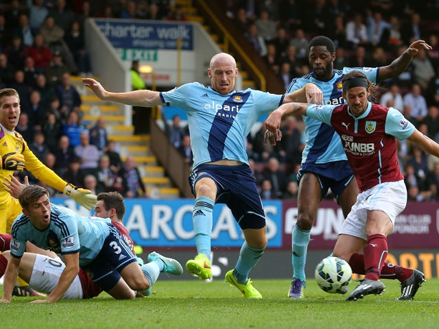 George Boyd of Burnley shoots past James Collins of West Ham to score his team's first goal during the Barclays Premier League match between Burnley and West Ham United at Turf Moor on October 18, 2014