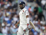 Indias Cheteshwar Pujara walks back to the pavilion after losing his wicket for 11 runs during play on the third day of the fifth cricket Test match between England and India at The Oval in London on August 17, 2014