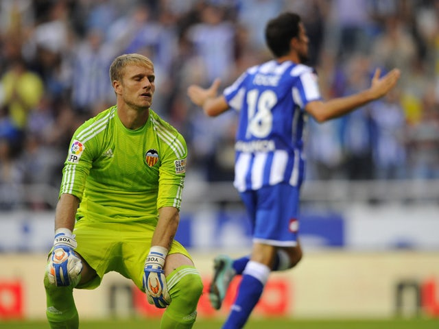 Valencia's goalkeeper Yoel Rodriguez reacts as Deportivo's forward Toche celebrates a goal during the Spanish league football match RC Deportivo de la Coruna vs Valencia CF at the Municipal de Riazor stadium in La Coruna on October 19, 2014