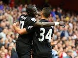 Mohamed Diame of Hull City celebrates with team-mate Hatem Ben Arfa after scoring their first goal during the Barclays Premier League match between Arsenal and Hull City at Emirates Stadium on October 18, 2014
