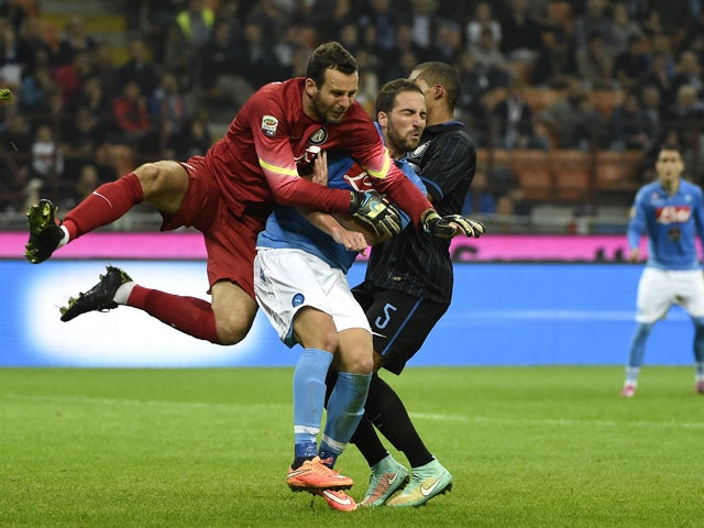 Inter Milan's goalkeeper from Slovenia Samir Handanovic jumps for the ball next to Napoli's forward from Argentina Gonzalo Higuain during the Italian Serie A football match Inter Milan vs Naples on October 19, 2014