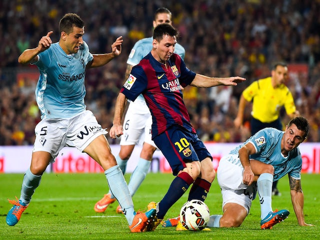 Lionel Messi of FC Barcelona duels for the ball with SD Eibar players during the La Liga match between FC Barcelona and SD Eibar at Camp Nou on October 18, 2014