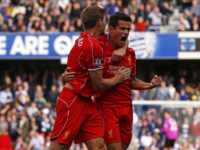 Liverpool's Brazilian midfielder Philippe Coutinho celebrates scoring his goal with Liverpool's English midfielder Steven Gerrard (L) during the English Premier League football match between Queens Park Rangers and Liverpool at Loftus Road in London on Oc