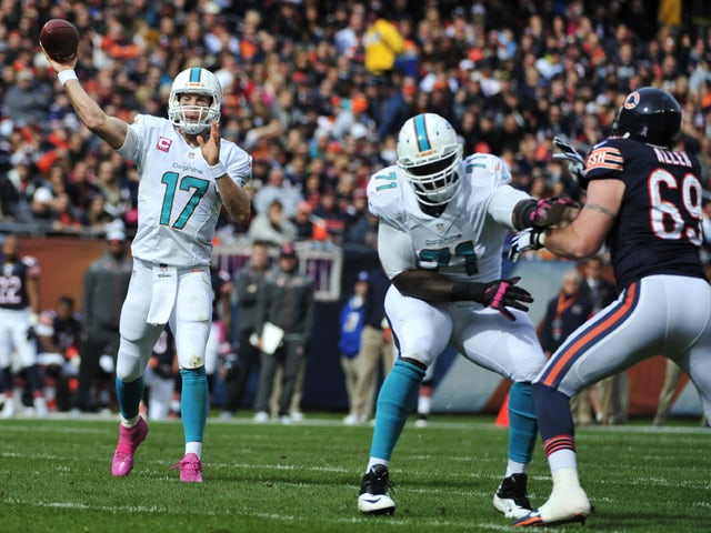 Ryan Tannehill #17 of the Miami Dolphins throws a touchdown pass as Branden Albert #71 of the Miami Dolphins blocks Jared Allen #69 of the Chicago Bears during the first quarter of the game at Soldier Field on October 19, 2014