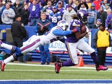 Cordarrelle Patterson #84 of the Minnesota Vikings scores a touchdown as Corey Graham #20 of the Buffalo Bills defends during the first half at Ralph Wilson Stadium on October 19, 2014
